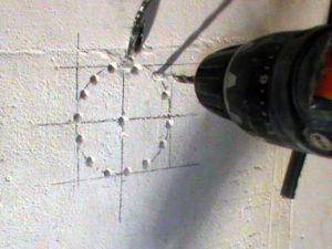 Просверливаем контур для подрозетника перфоратором